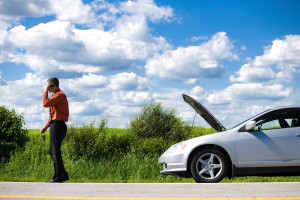 Man with cell phone on roadside by car breakdown